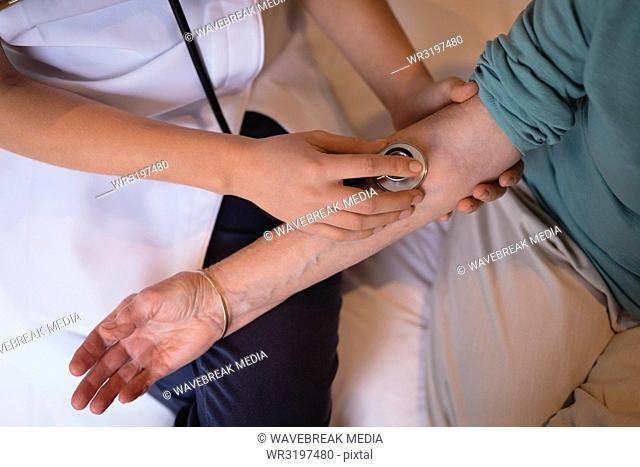 Physiotherapist examining senior woman with a stethoscope