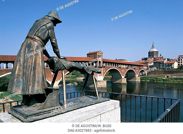 The bronze washerwomen monument, with the covered bridge (Old bridge) over the Ticino river in the background, Pavia, Lombardy, Italy