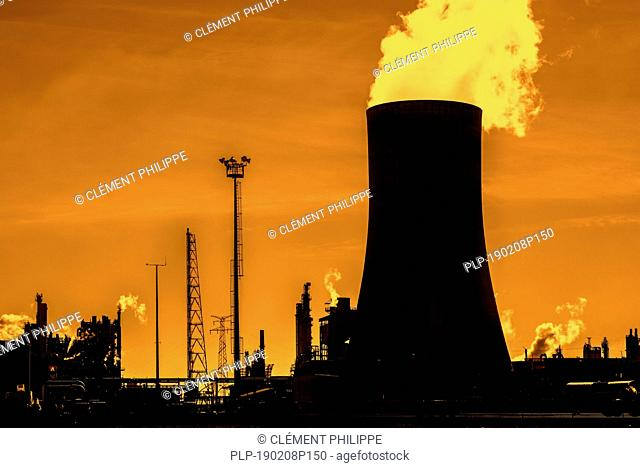 Industrial estate showing cooling tower silhouetted against sunset at the BASF chemical production site in the port of Antwerp, Belgium