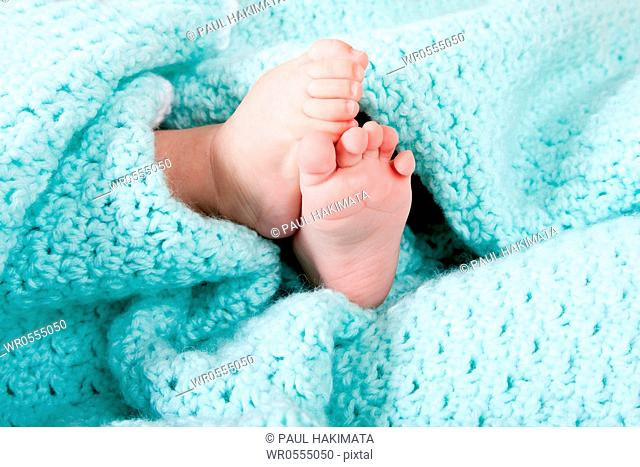 Two cute tiny baby feet wrapped in a blue-green aqua knitted blanket