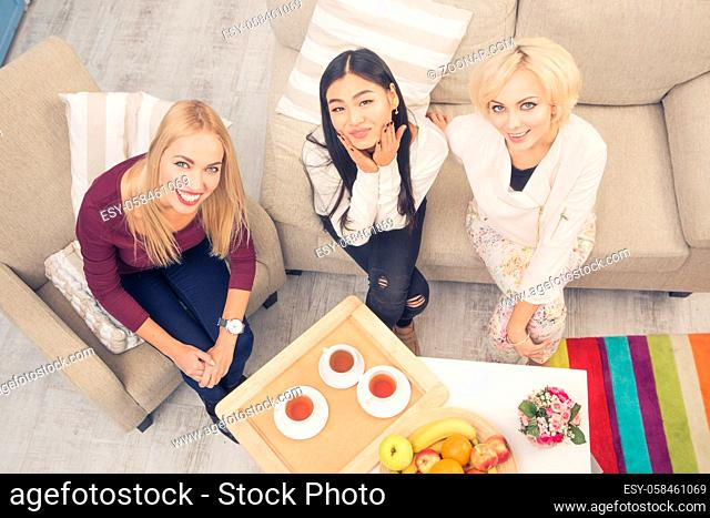 Toned top view picture of friends girls sitting on sofa or couch. Beautiful ladies ready for having tea. Women smiling for camera. Home party concept