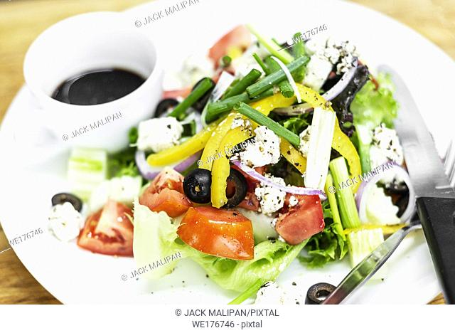 traditional greek salad with feta cheese and mixed organic vegetables on wooden table