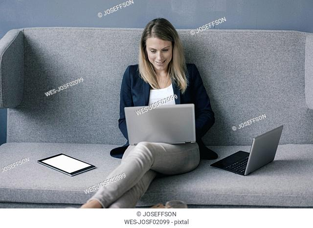 Smiling businesswoman sitting on the couch using laptop