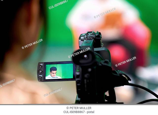 Over shoulder view of college students practicing in TV studio with green screen