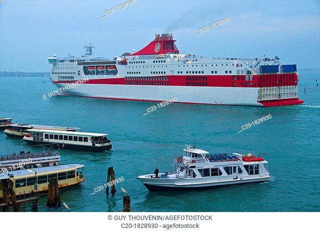 Passenger touristic boat with vaporetto, and cruise boat on canal in front of Venice, Italy