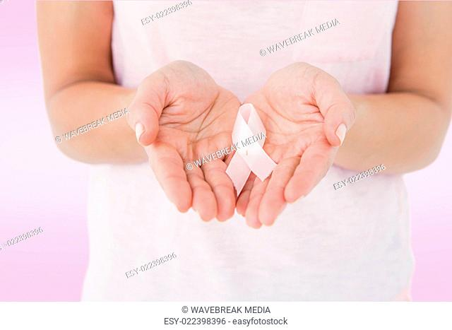 Composite image of woman holding pink ribbon for breast cancer awareness