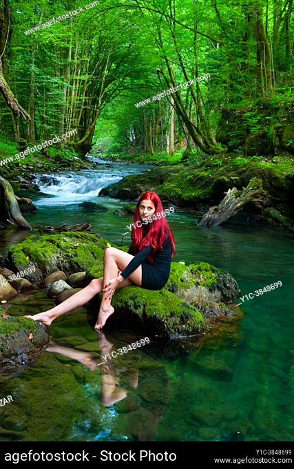 Young woman in Green forest sitting near a small river is looking away