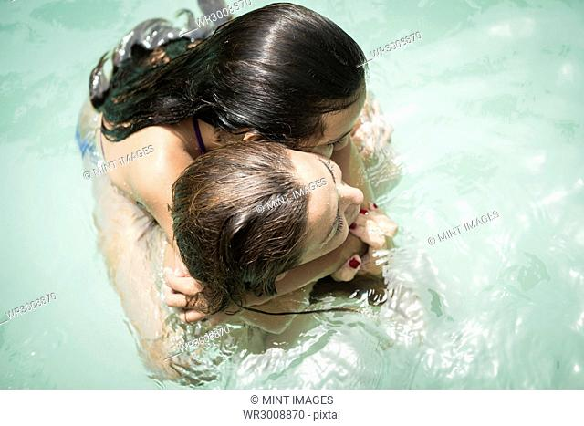 High angle view of a woman and a girl hugging in a swimming pool