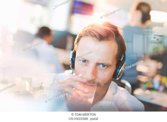 Businessman with headphones drinking water in office