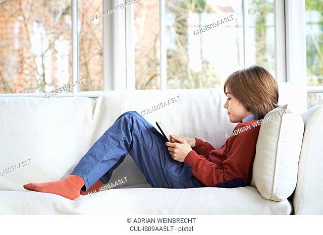 Boy on sofa using digital tablet