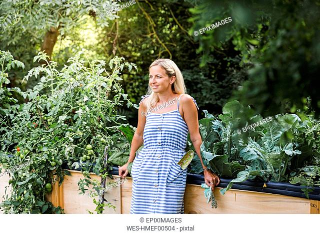 Blond woman standing in front of her raised bed in her own garden