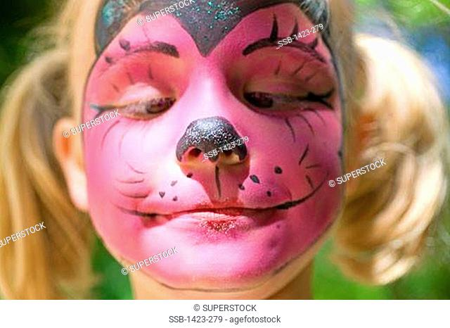 Close-up of a girl with her face painted as cat