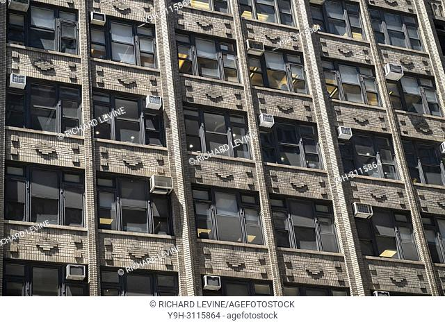 Air conditioners sprout from windows in an older office building in New York on Thursday, May 24, 2018. (© Richard B. Levine)