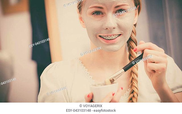 Facial dry skin and body care, complexion treatment at home concept. Happy young woman applying grey mud mask on her face with brush