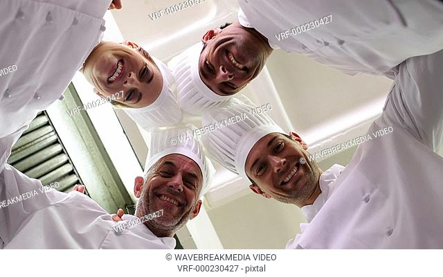 Team of chefs standing in circle looking down at camera in a commercial kitchen