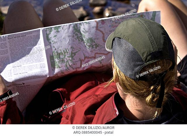 A young woman looks at a trail map on the Teton Crest Trail