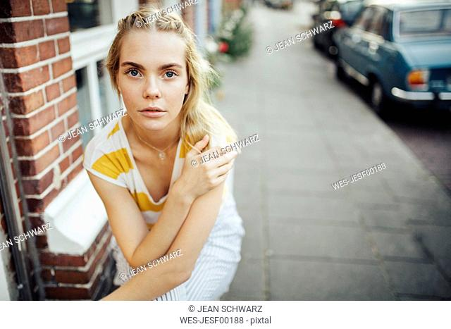 Portrait of young woman sitting in front of house
