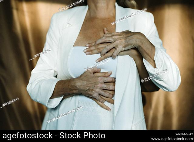 Hands embracing mother from behind