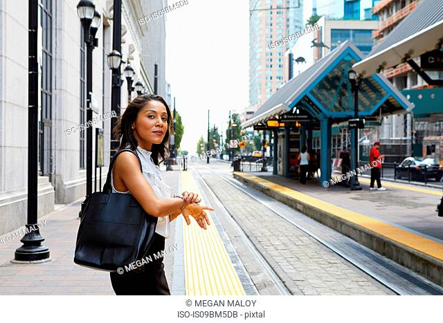 Businesswoman checking time by light rail line