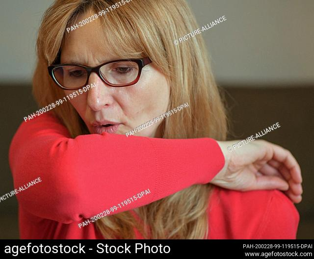 ILLUSTRATION - 27 February 2020, Brandenburg, Sieversdorf: A woman coughs into the crook of her arm (posed photo). When coughing or sneezing