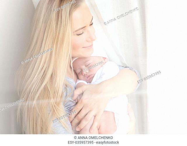 Portrait of a nice mother with closed eyes of pleasure holding adorable newborn sleeping baby, happy motherhood concept