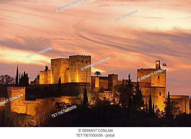Illuminated castle at dusk, pastel colored clouds in sky