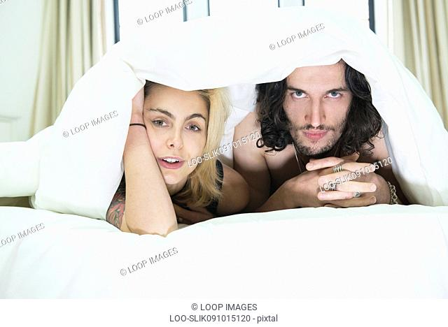A cool young tattooed couple peeking out from under a duvet on a bed