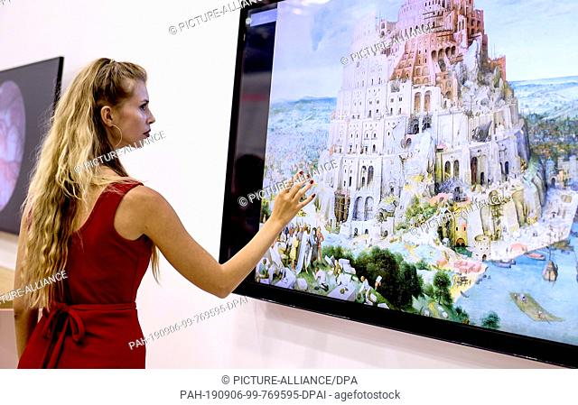 06 September 2019, Berlin: A young woman presents a touch screen at the IFA, the world's largest trade fair for consumer electronics