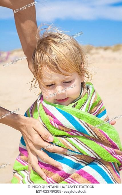summer family scene of two woman mother hands drying a two years blonde baby wrapped in colorful towel at beach sand