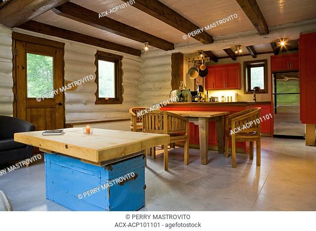 Blue chest coffee table in living room area plus wooden breakfast table with three chairs and view of kitchen with red painted wooden cabinets on the 1st floor...
