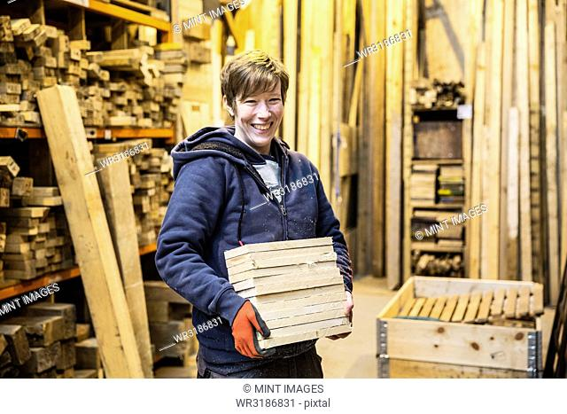 Smiling blond woman wearing work gloves standing in a workshop, holding stack of wood, looking at camera