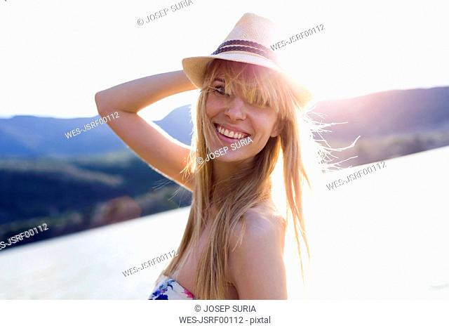 Portrait of smiling young woman in front of lake wearing summer hat at dusk