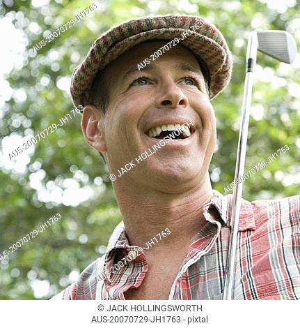 Close-up of a mature man holding a golf club and laughing