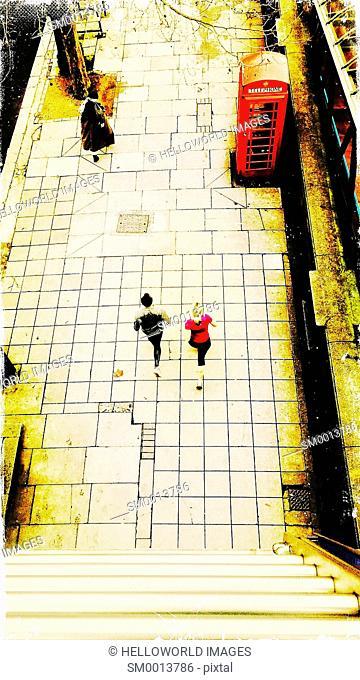 Runners passing iconic British red telephone box, Victoria Embankment, London, England, Europe