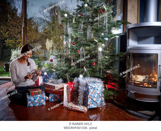 Woman unwrapping Christmas gifts under Christmas tree