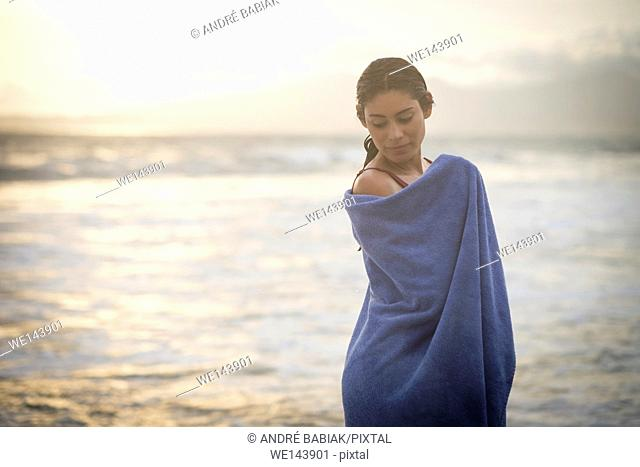 Sunset portrait of young hispanic woman wrapped in a towel at a beach