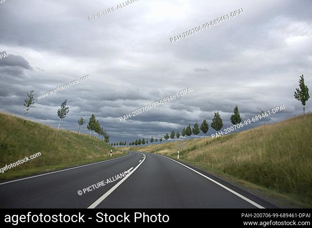 05 July 2020, Saxony-Anhalt, Gernrode: Dark clouds hang over a country road near Gernrode in the Harz Mountains. To the left and right of the road small trees...