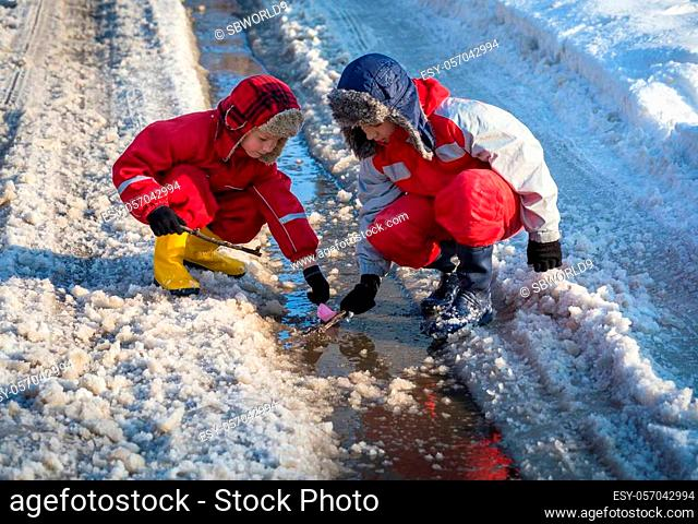 Two boys in rainboots launching the paper boat at the creek with melting snow on sunny spring day, outdoors