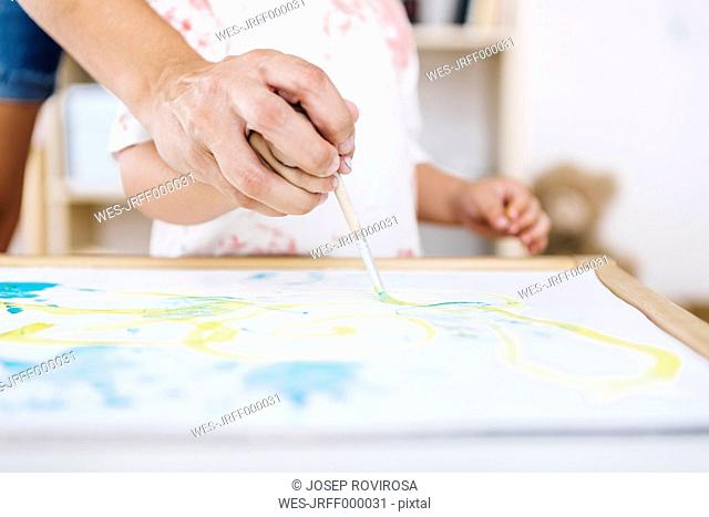 Woman helping little boy to paint with watercolours, close-up
