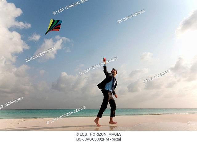 Businessman flying a kite on beach