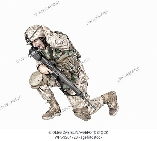 Army soldier in camo uniform, armed with assault rifle and machine gun, crouching to ground, holding helmets and covers ears with hands isolated on white studio...