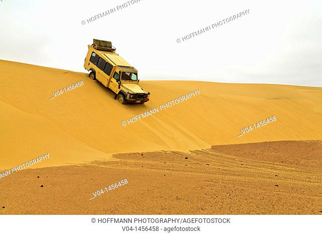 A landrover driving down a dune in the desert of the Skeleton Coast Park, Namibia, Africa