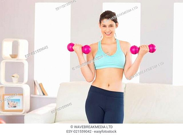Fit brunette holding pink dumbbells