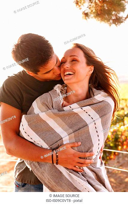Couple hugging in vineyard, Cape Town, South Africa