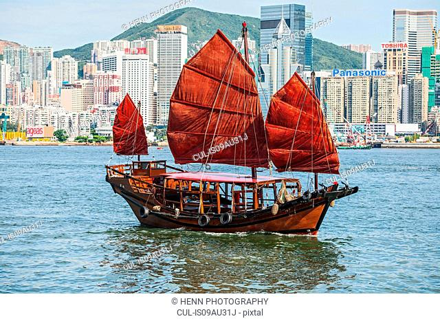Traditional Chinese junk sailing at Victoria harbour in Hong Kong, China