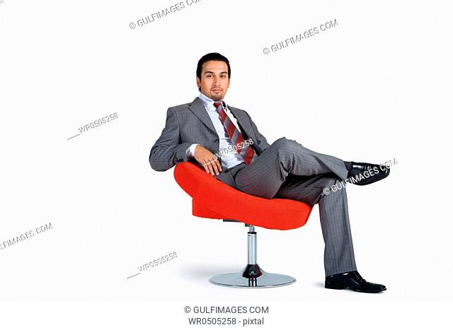 Young businessman sitting on swivel chair, portrait