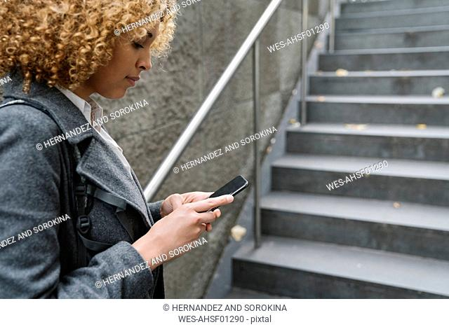 Woman using smartphone at the entrance of a subway station, Berlin, Germany