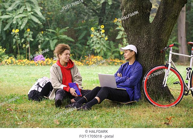 Man with laptop talking to friend while sitting on grassy field at park