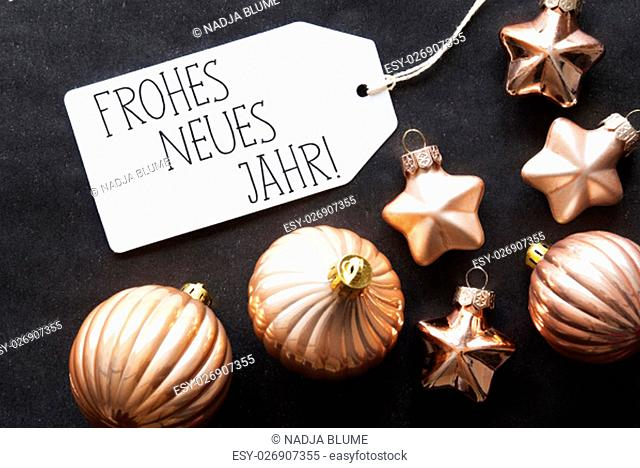 Label With German Text Frohes Neues Jahr Means Happy New Year. Bronze Christmas Tree Balls On Black Paper Background. Christmas Decoration Or Texture