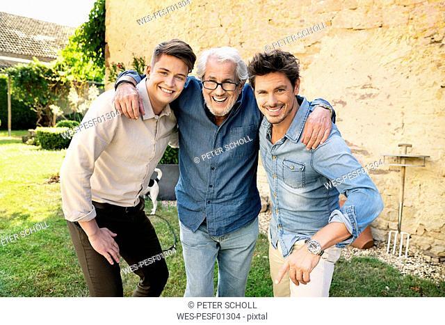 Portrait of three happy men of different age embracing in garden